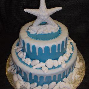 Gâteau en pâte de sucre orné de coquillages et d'une étoile de mer. Joli gâteau pour les amateurs de plage. Fait sur mesure, pour plus d'information contactez-nous.