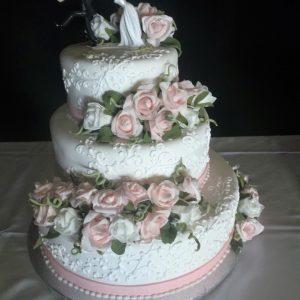 Gâteau de mariage 3 étages blanc et rose. Avec rose en pâte de sucre et silouhette de la mariée qui agrippe le marié en ornement. Fait sur mesure, pour plus d'information contactez-nous.