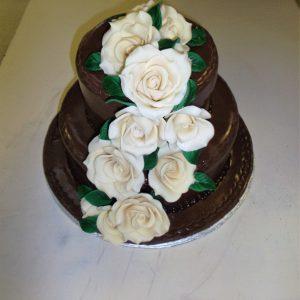 Gâteau de mariage fait sur mesure avec roses blanches en pâte de sucre. Saveur chocolat. Fait sur mesure, pour plus d'information contactez-nous.
