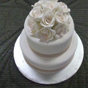 Gâteau de mariage 2 étages avec roses blanches au sommet. Simple, épuré et magnifique. Fait sur mesure, pour plus d'information contactez-nous.