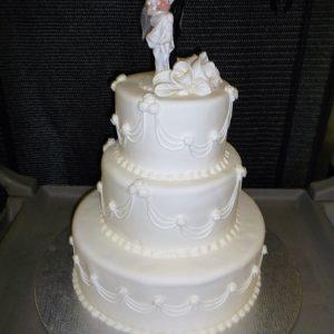 Gâteau de mariage blanc immaculé avec figurine des mariés en ornement. Avec fleurs blanches en pâte de sucre. Fait sur mesure, pour plus d'information contactez-nous.