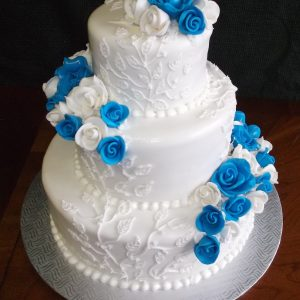 Gâteau de mariage 3 étages en pâte de sucre. Décoré de fleurs blanches et bleues. Fait sur mesure, pour plus d'information contactez-nous.