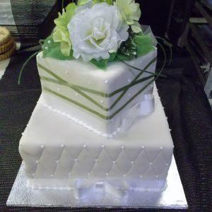 Gâteau de mariage sur mesure en pâte de sucre. Orné de rubans blancs et de fleur. Fait sur mesure, pour plus d'information contactez-nous.