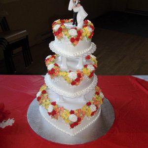Gâteau de mariage fait sur mesure. 3 étages en forme de coeur sur des pilliers blanc. Orné de fleurs blanches rouge et jaunes. Fait sur mesure, pour plus d'information contactez-nous.