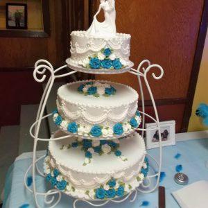 Gâteau de mariage fait sur mesure. 3 étages sur un support blanc. Avec figurine des mariés et fleurs blanches et bleus en ornement. Fait sur mesure, pour plus d'information contactez-nous.