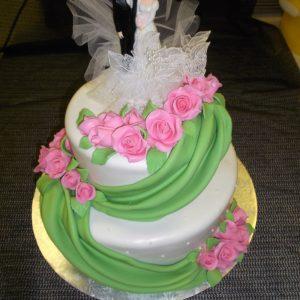 Gâteau de mariage 2 étages en pâte de sucre. Décoré de roses et d'un voile vert. Fait sur mesure, pour plus d'information contactez-nous.